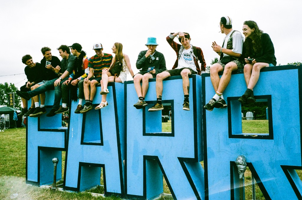Revelers sit upon the Farr sign, looking out over the rolling hills